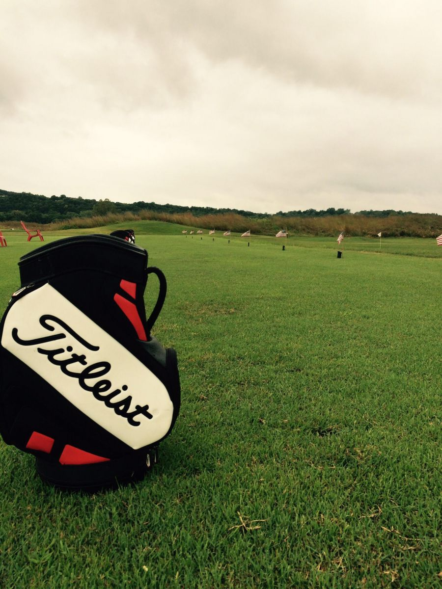 Titleist golf bag sitting on grass at driving range
